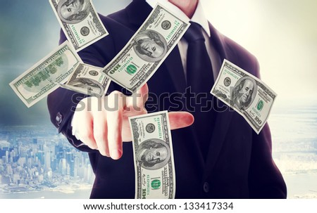Business man with hundred dollar bills on big city backdrop