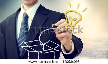Business man with Idea light bulb coming 'out of the box' with a big city backdrop - stock photo
