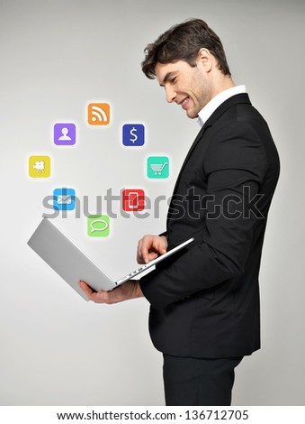 Business man with laptop in hand and media icon over grey background