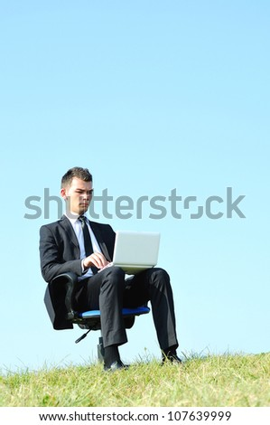 Business man with laptop on chair