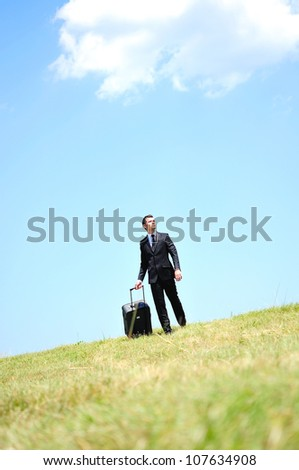 Business man with luggage in nature