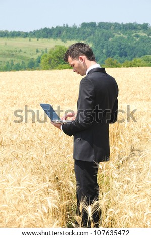 Business man with notebook on field