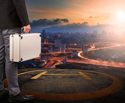 business man with strong metal briefcase standing on helicopter pad on top of building roof with sun rising over urban scene