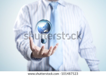 Business man with the digital globe inside light bulb floating on his hand. Concept for idea of connectivity within grasp. - stock photo