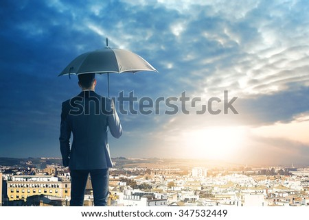 Business man with umbrella observing the sunset on the city