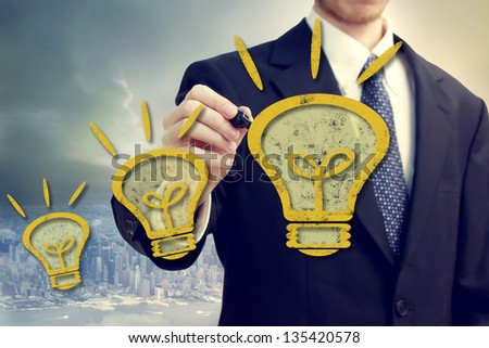 Business man with yellow idea light bulbs above a big city backdrop