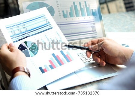 Business man working and analyzing financial figures on a graphs on a laptop outside