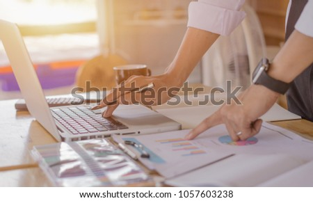 Business man working at office with laptop, tablet and graph data documents on his desk. #1057603238