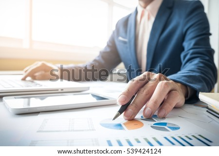 Business man working at office with laptop, tablet and graph data documents on his desk.