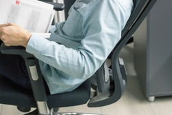 Business man working on his computer in an ergonomic office chair