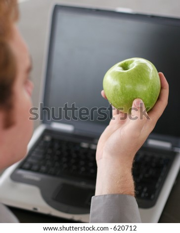 business man working on his laptop with an apple in his right hand