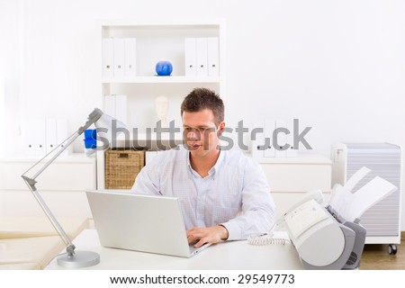 Business man working on laptop computer at home.