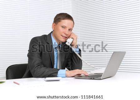 Business man working on laptop computer at office and calling on phone