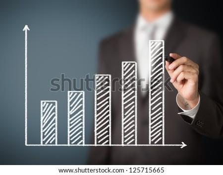 business man writing growth bar chart