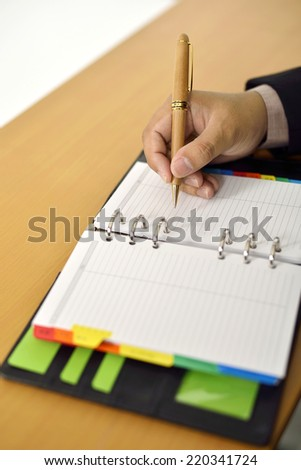 Business Man writing on agenda on the desk