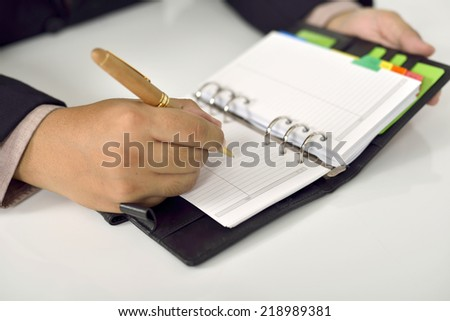 Business man writing on agenda over office desk
