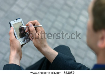 Business man writing on his pda - stock photo