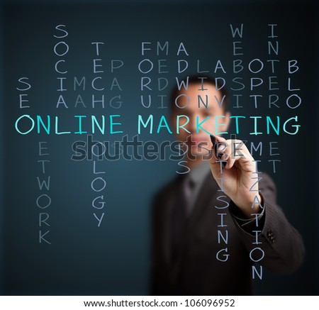 business man writing online marketing  concept by crossword of relate word such as internet, technology, advertising, seo, website, media, etc.