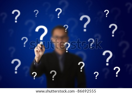 business man writing question mark