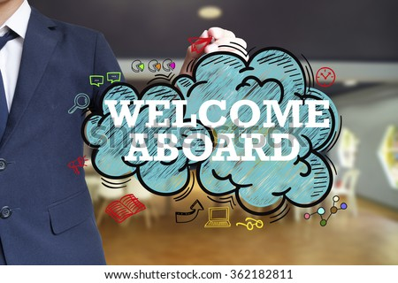 business man writing WELCOME ABOARD  over the cloud with office background , business concept , business idea