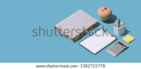 Business management and finance: paperwork, money box, calculator and office supplies, isometric objects, blank copy space stock photo