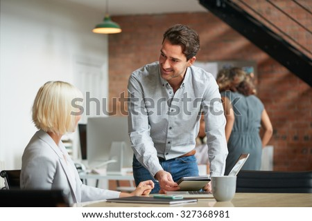 Business manager discussing work with colleague in busy office studio