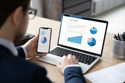 Business marketer using professional app for marketing data analyzing on laptop and smartphone screens, studying financial graphs, comparing diagrams on phone and computer. Analysis concept