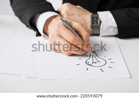 business, marketing, planning and people concept - close up of male hands with pen drawing bulb on white paper #220593079