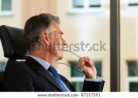 Business - mature boss contemplating in his office; he is looking out of the window