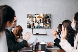 Business meeting.A group of formal successful people wearing protective masks sit at the table and communicate online via videoconference with colleagues discussing about important business strategies