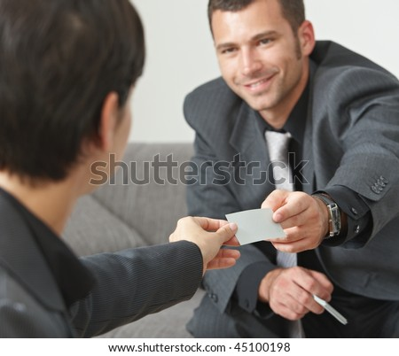 Business meeting at office lobby, people sitting on sofa changing business cards. Focus on card.