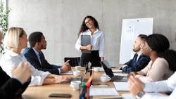 Business Meeting Concept. Mexican Businesswoman Presenting Startup Idea To Coworkers Standing Near Blackboard In Modern Office. Business Presentation. Selective Focus, Panorama
