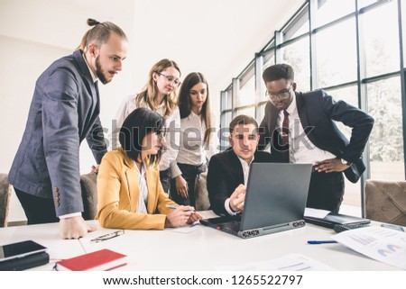 Business meeting of multinational managing team with laptops in office. Multiethnical group of business people having a business meeting