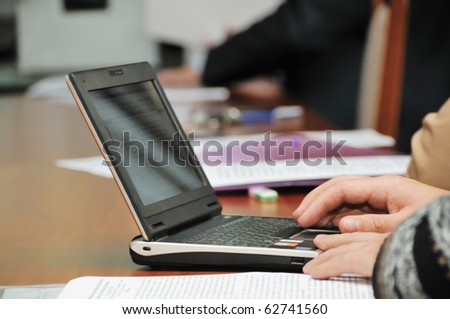 Business meeting or conference, focus on businessmans hands on the net-book
