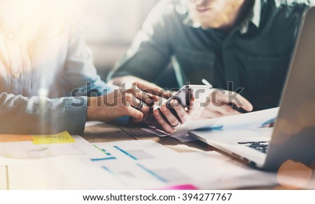 Business meeting partners. Photo young businessmans crew working with new startup project in modern loft. Generic design smartphone holding female hands. Horizontal, film effect