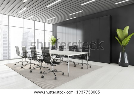 Business meeting room with black armchairs and white table, side view, grey carpet on white floor. Black shelf and two plants, windows with city view, 3D rendering no people