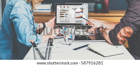 Business meeting. Teamwork. Businessman and businesswoman sitting at table in front of laptop and working. Man shows pencil on computer screen.Graphs,charts and diagrams on PC screen.Online education.