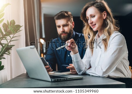 Business meeting. Teamwork. Businesswoman and businessman sitting at table in front of laptop and working. Woman shows pencil on computer screen. Online marketing, e-commerce. Business education.