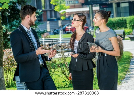Business meeting. Three successful business people in formal clothes standing on the street to discuss business and keep computers in their hands. Young businessmen talking to each other