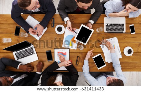 Business meeting top view. Busy people work in office, above view of wooden table with mobile phones, laptop, tablet and documents papers with diagram. #631411433