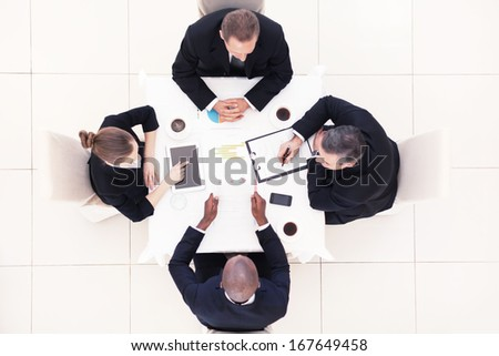 Business meeting. Top view of four business people in formalwear sitting at the table and discussing something