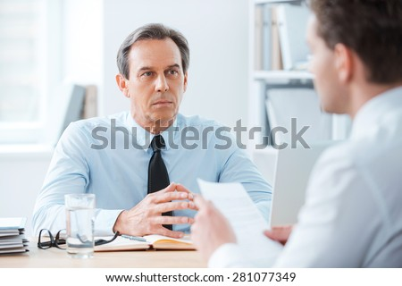 Business meeting. Two business people sitting in front of each other in the office while discussing something