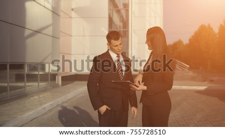 Business meeting. Young beautiful businesswoman talks and shows documents to young male employee outdoors against backdrop of business center. sunlight