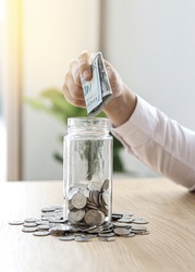 Business men grabbing dollar bills to put in a glass jar with a handful of coins inside and piled on the outside of a glass jar, business men regularly save money to invest.