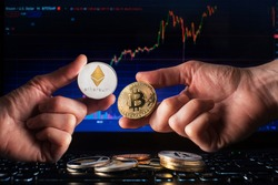 Business men holding bitcoin and ethereum coin whit computer trading chart background. Bitcoin and altcoin the most important cryptocurrency concept
