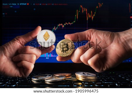 Business men holding bitcoin and ethereum coin whit computer trading chart background. Bitcoin and altcoin the most important cryptocurrency concept Stockfoto ©