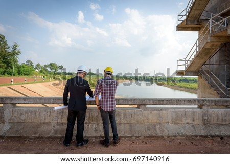 Business men meeting with Engineers and supervisors are standing reading the blueprints at the construction site.