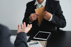 Business men pull or collect Illegal money, bribes in brown envelopes To bribe his partner in illegal business practices, the idea of giving and receiving illegal bribes.