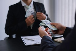 Business men pull or collect Illegal money, bribes in the form of cash To bribe his partner in illegal business practices, the idea of giving and receiving illegal bribes.
