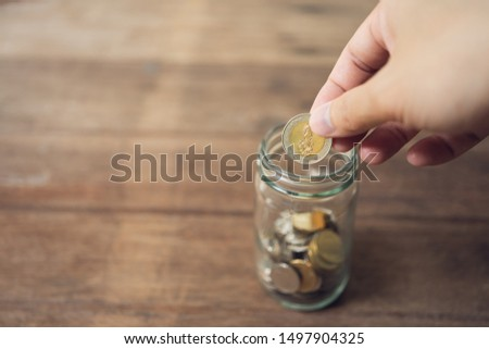 Business men Put the coin in a glass jar To save money, save money on investments, spend money when needed And use in the future. Investment concept. Savings with copy spaces. #1497904325
